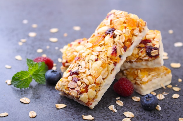 Healthy snack, muesli bars with raisins and dried berries on a black background