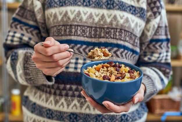 朝のヘルシーなおやつや朝食。ミューズリーボウルを持つ若い女性。ボウルにナッツ、カボチャの種、オート麦、ヨーグルトと一緒に朝食用シリアルを食べる女の子。自家製グラノーラを持っている女の子。