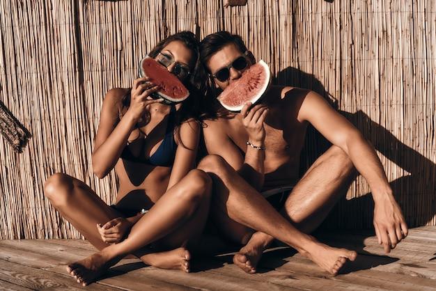 Здоровые закуски. красивая молодая пара, прикрывая половину лица ломтиком арбуза, сидя на открытом воздухе