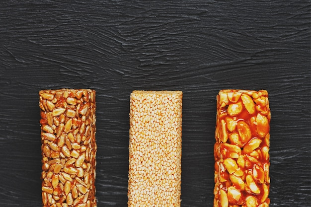 Healthy snacks. fitness diet food. grain bar with peanuts, sesame and seeds on a cutting board on a dark table, energy bars