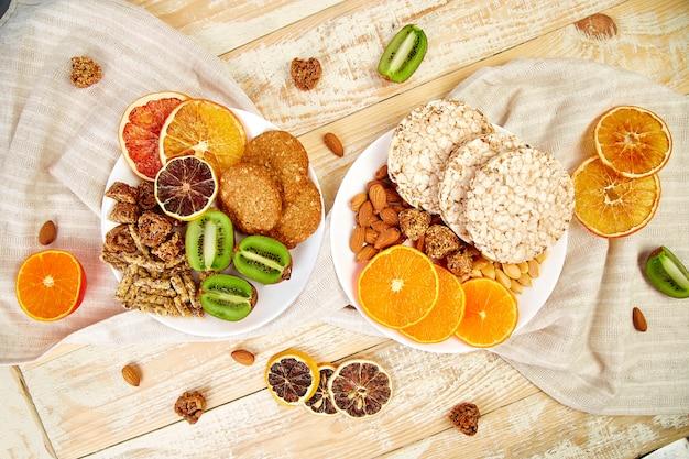 Healthy snacks variety oat granola bar,  rice crips, almond,  kiwi, dried orange