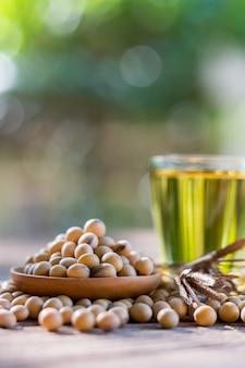 木の床に健康な大豆、木製のカップ、木のスプーンをグループで一緒に、コピースペース