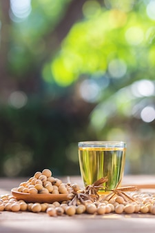Healthy soybean on wooden floor, wooden cup, wooden spoon together as a group, copy space