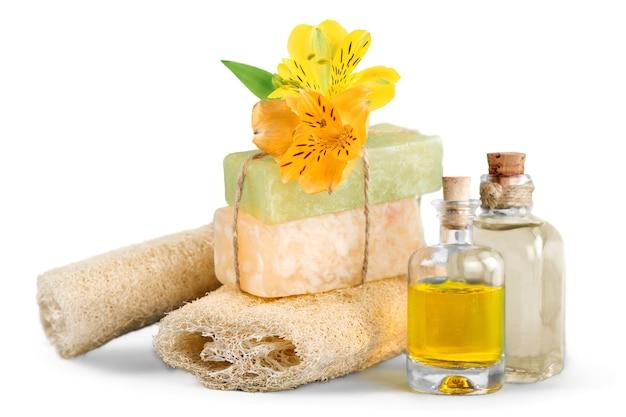 手作り石鹸バー、オイルボトル、スポンジ、花を使ったヘルシーなスパコンセプト