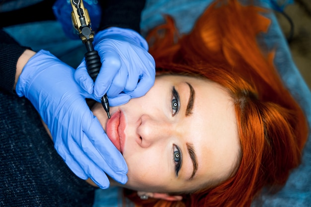 Healthy spa: young beautiful woman having permanent makeup tattoo on her lips. close-up