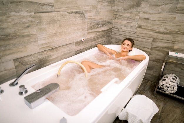 Healthy spa. young caucasian beautiful relaxing woman lying in the bath with hydro massage.