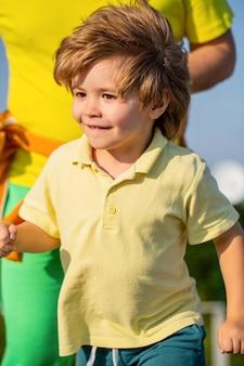 子供のための健康的なスポーツ活動。父と息子はスポーツをして走ります。子供のためのスポーツ、アクティブな子供が走っています。子供は屋外で走ります。スタジアムで走っている子供。子供のためのジョギング。