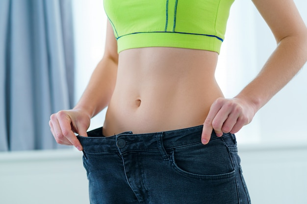 Healthy sport fitness woman with slim waist pulling her big jeans and showing weight loss and diet results. achieving weight loss goals, motivation and progress in slimming