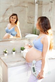 Здоровый спорт красивая беременная женщина в ванной смотрит в зеркало, держа стакан воды и весы. здоровое питание. вес при беременности. образ жизни. фото высокого качества