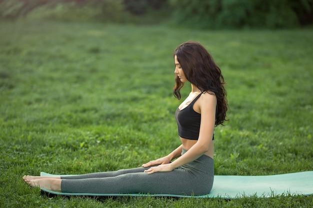 健康的なスポーツライフスタイル。体を伸ばすためのトレーニングをしている若い女性。若い魅力的なスリム