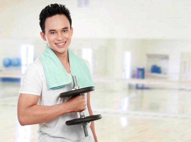 ダンベルを笑顔で健康的なスポーツの男
