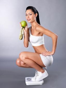 健康的なスポーツの女性は体重計の上に立って体重をチェック