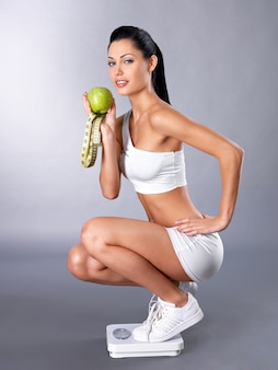 Healthy sports woman stands on the scales and checks her  weight