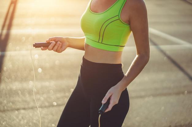 Здоровая спортсменка в спортивной одежде, делая кардио упражнения с скакалка на открытом воздухе. быть в форме и вести спортивный образ жизни