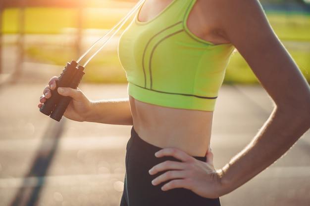 屋外の縄跳びで演習を行うスポーツウェアで健康的なスポーツウーマン。体調を整え、スポーツライフスタイルを持つ