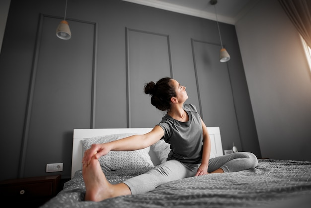 Healthy sporty shape middle aged woman doing seated yoga poses on the bed in the morning.