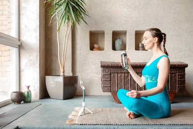 オンラインでヨガを練習するためにスマートフォンを使用しながら、スポーツボトルから水を飲む体操衣装で健康的なスポーティなスリムな女性。