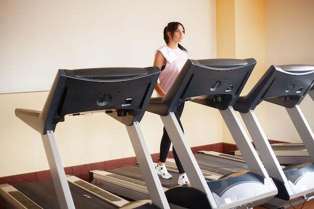 Здоровая спортивная женщина делает кардио-упражнения на беговой дорожке.