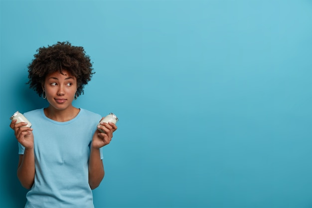 Healthy sporty woman with afro hair holds glass jars of fresh yoghurt, going to prepare breakfast, has proper nutrition, concentrated aside, wears casual clothes, poses against blue wall