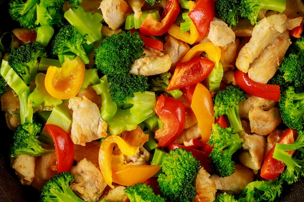Healthy stir fry vegetables with chicken in pan on white surface close up.