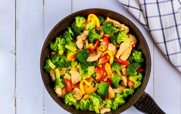 Healthy stir fry vegetables with chicken in pan on white surface.
