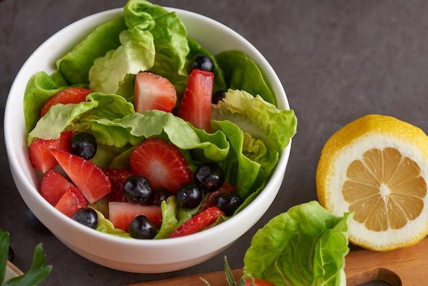 Салат из здоровой клубники с телятиной, ежевикой в белой тарелке.