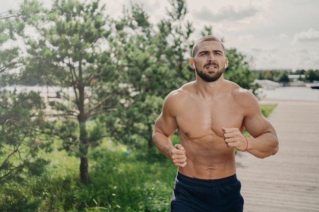 Healthy strong bearded man runner has jogging exercise in open air, breathes deeply and listens music in earphones, has naked torso, strong muscular arms. morning workout and active lifestyle concept