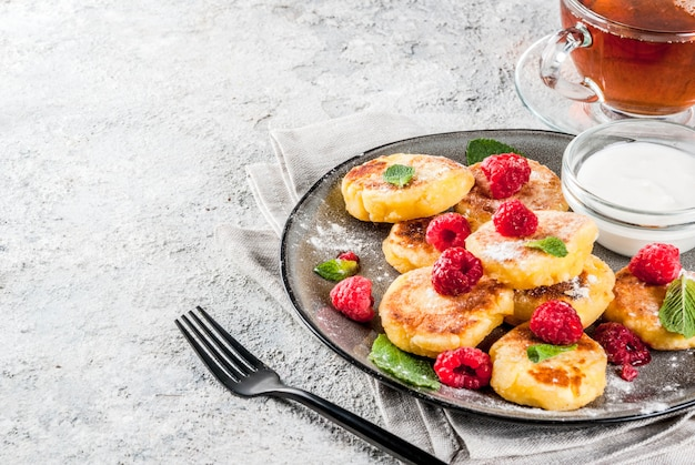 Healthy summer breakfast cheese pancakes with raspberry powdered sugar and mint grey concrete background