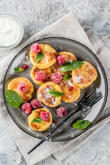 Healthy summer breakfast, cheese pancakes with raspberry, powdered sugar and mint, grey concrete table copy space