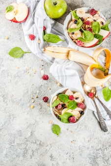 Healthy summer breakfast fruit and berry salad with spinach granola apple and banana white marble background