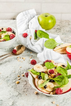 Healthy summer breakfast, fruit and berry salad with spinach, granola, apple and banana, white marble surface