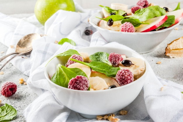 Healthy summer breakfast, fruit and berry salad with spinach, granola, apple and banana