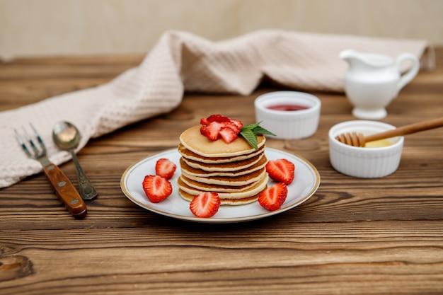 Здоровый летний завтрак, домашние классические американские блины со свежими ягодами и медом на деревянном фоне. вкусная выпечка, десерт.