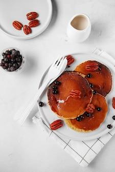 健康的な夏の朝食、新鮮なベリー、ナッツ、蜂蜜と自家製の古典的なアメリカのパンケーキ、朝のライトグレーの石の背景コピースペースの上面図。フラットレイ構成
