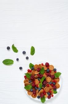健康的な夏の朝食小さなパンケーキ新鮮なベリーとミントの葉の白い木製のテーブルのトップビュー