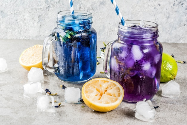 Healthy summer cold beverage, iced organic blue and violet butterfly pea flower tea with limes and lemons