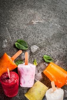 Здоровые летние десерты. фруктовое мороженое. замороженные тропические соки, смузи черника. смородина, апельсин, манго, киви, банан, кокос, малина. на черном каменном столе скопируйте пространство сверху