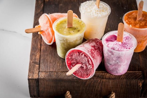 Здоровые летние десерты. фруктовое мороженое. замороженные тропические соки, смузи черника. смородина, апельсин, манго, киви, банан, кокос, малина. на белом мраморном столе, деревянный поднос