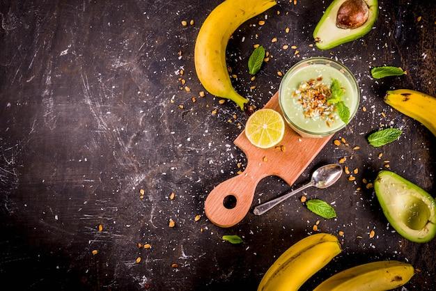 健康的な夏の飲み物、ライム、グラノーラ、ココナッツミルク、暗いさびた背景コピースペースとアボカドとバナナのスムージー
