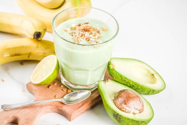 健康的な夏の飲み物、ライム、グラノーラ、ココナッツミルクとアボカドとバナナのスムージー