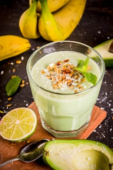 Healthy summer drink avocado and banana smoothie with lime granola and coconut milk dark rusty background