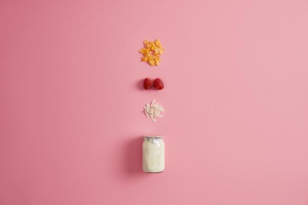 Superfood sano e concetto di nutrizione organica. vasetto di yogurt fresco e tre ingredienti nutrienti per preparare la colazione. granola, lampone rosso e fiocchi di cocco su sfondo rosa.
