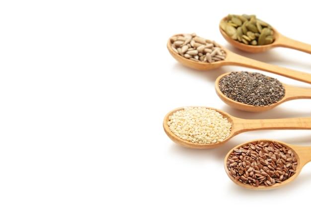 健康的なスーパーフード:ゴマ、カボチャの種、ヒマワリの種、亜麻の種、白で分離されたチア。スプーンの種