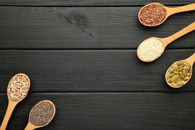 健康的なスーパーフード:ゴマ、カボチャの種、ヒマワリの種、亜麻の種、黒のチア。スプーンの種