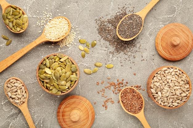 健康的なスーパーフード:灰色の背景にゴマ、カボチャの種、ヒマワリの種、亜麻の種、チア。スプーンの種