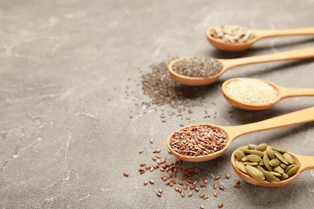 Healthy superfood sesame, pumpkin seeds, sunflower seeds, flax seeds and chia on grey.