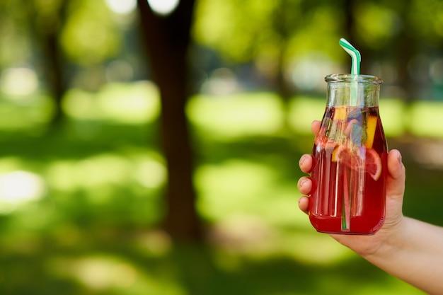 녹색 흐리게 여름 배경에 손에 건강 한 달콤한 감귤 해독 음료. 야외에서 신선한 차가운 차 항아리