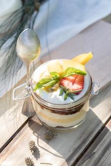 Здоровый сладкий йогуртовый десерт с фруктами в стеклянной банке