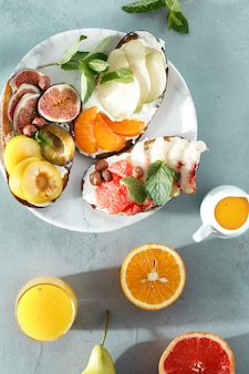 Healthy tasty breakfast sandwiches fruit top view stone