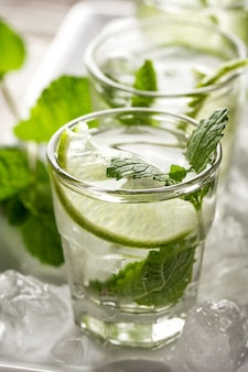 Healthy tasty fresh refreshing detox water in glasses with lime, mint and ice on wooden background. closeup. healthy life concept.